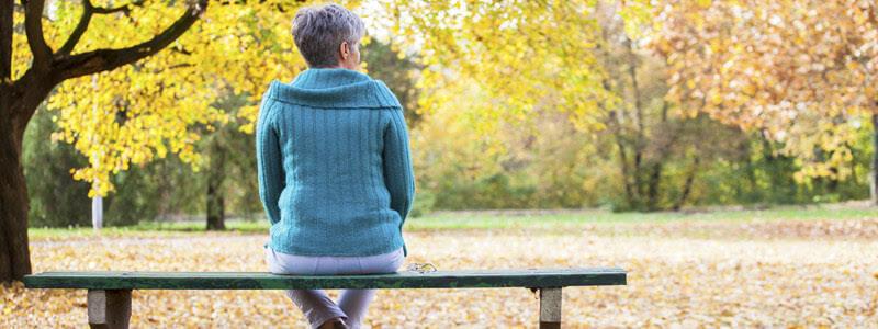 Frau sitzt auf Bank im Wald
