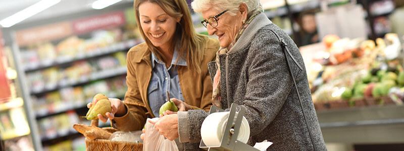 Junge und alte Frau beim Einkaufen